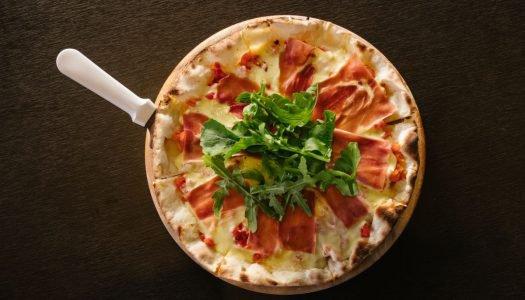 Pizza de presunto de parma e uma taça de Divinum Reserva Carménère